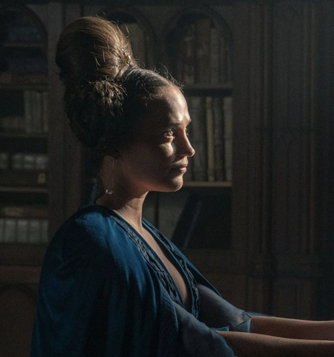 Alicia Vikander in Sir Gawain and the Green Knight, wearing teal velvet and sheers. Her hair is up in an intricate braided bouffant. Light is on one half of her face, her brown eyes are almost caramel.