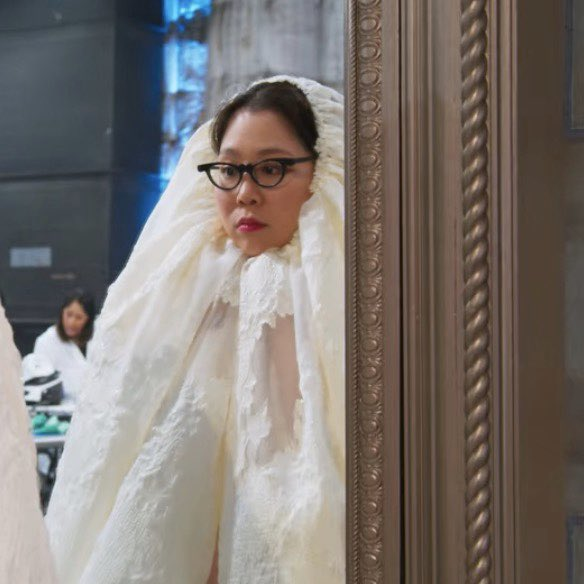 Minju Kim, a fashion designer on the Netflix show Next in Fashion, looks pensive as her face pokes out of a lace veil.