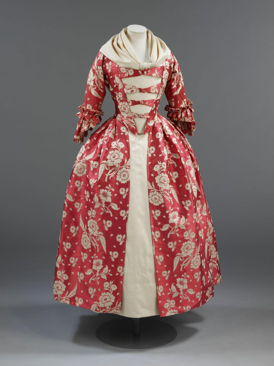 This 1760s gown features a rose-red silk with trails of ivory flowers woven in a complex technique. The fabric, a type of silk known as gros de tours, dates from the 1740s, but the gown itself has been remade into the style of the 1760s.  Due to the great expense of silk, it was very common practice in the 18th century for women to remake and update their gowns. Gros de tours silks were luxury fabrics in the 1740s, costing between 6 shillings and twelve shillings per yard; a sack required some fifteen yards of silk.