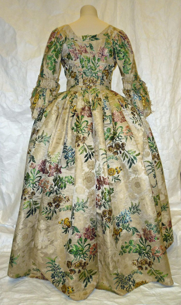 ©Victoria & Albert Museum, London - Woman's gown of ivory silk satin figured in a floral design and brocaded with coloured silks in a pattern of large flowers and leaves. The gown is front opening, the bodice lined with linen. It has a fitted back and elbow-length sleeves with double, scalloped ruffles. The skirts are made of 6 lengths of silk, gathered into a waist seam.  The gown was probably first made 1745-50 and then altered in the 1760s to update the style and possibly for another wearer. The hem was taken up, the robings altered and the top sleeve ruffles converted to cuffs and white silk fringe added. The gown was later altered in the late 19th century for fancy dress. The side seams of the bodice were taken in and the waist seam reconfigured. Ties were added on the inside skirts to create a polonaise/bustle effect and the sleeve ruffles and front skirt panels lined with ivory silk sarsenet.