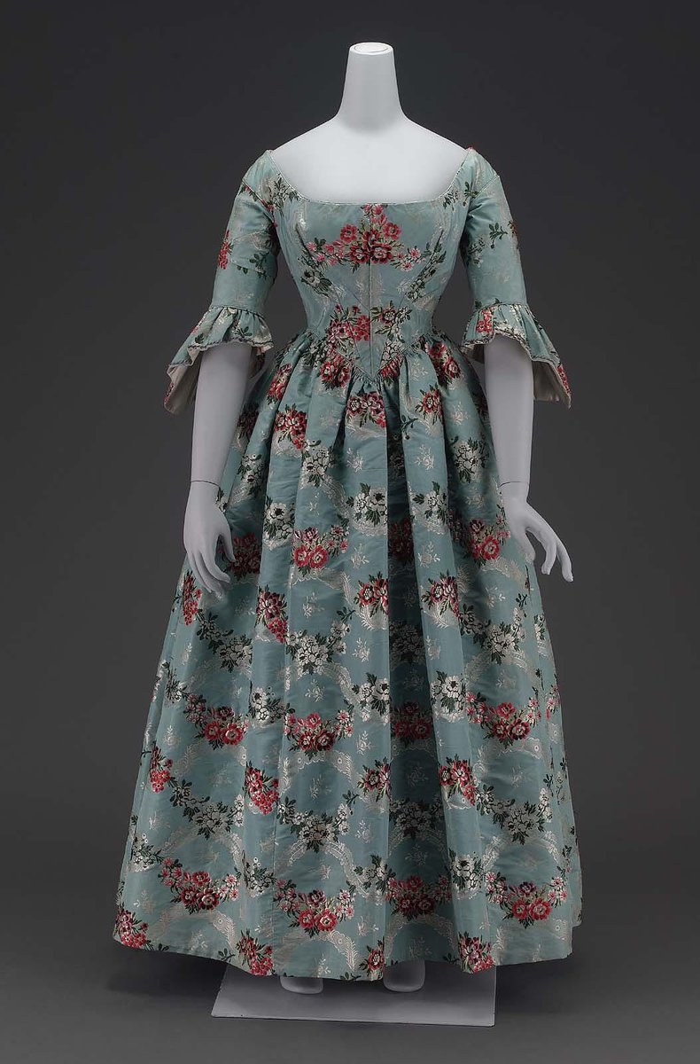 American, mid 19th about 1840. Fabric 18th century Spitalfields brocade, blue ground, horizontal interlacing ribbon and floral serpentines, brocaded with white and brilliant polychrome silks, tightly fitted bodice coming to V in center front, hooked down center back, wide flaring neckline, elbow length sleeves with sleeve ruffles shaped like those of the 18th century, full skirt with fullness gathered evenly all around.