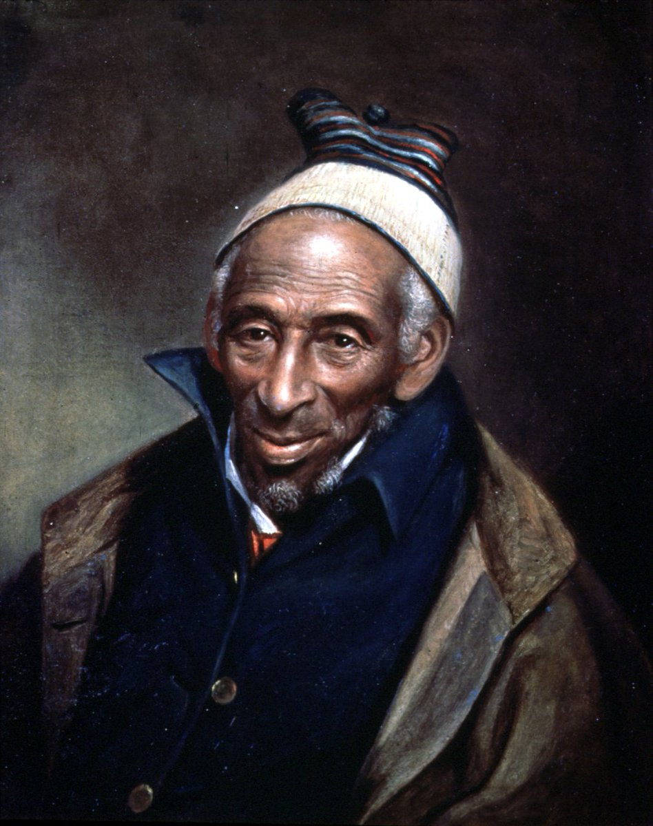 A man in a brown coat with a white knit cap, striped. He has brown skin, and brown eyes, and grey hair. He wears a high buttoned up jacket with wide lapels.