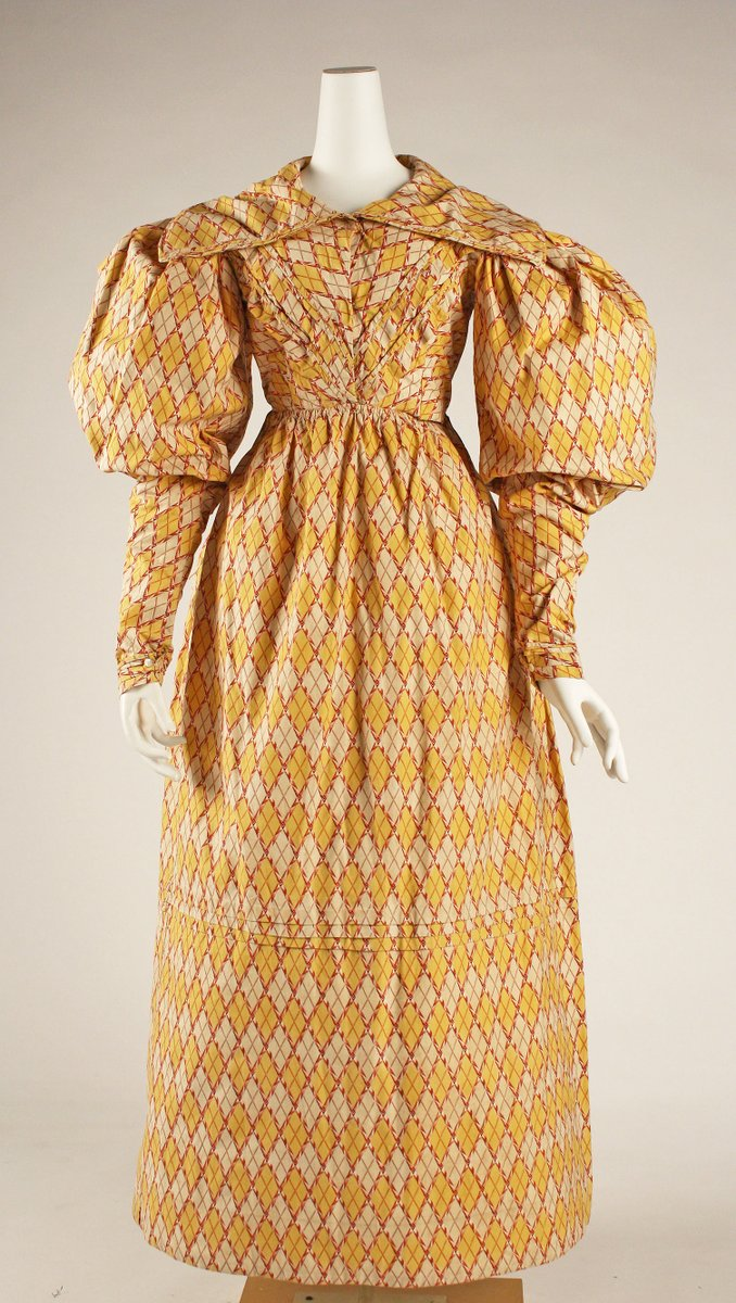 A classic Romantic silhouette gown with diamond pattern, huge puffy sleeves, and pleated bodice. The drop waist is gone, and the sleeves are long. Printed cotton in pale and bright yellow.