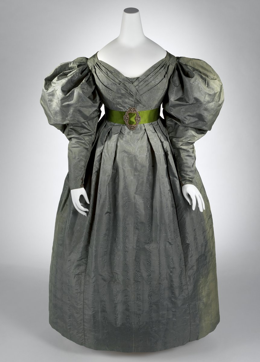 A grey-green silk gown in moiré silk. We're getting more of a bell silhouette in the skirt, but we still have huge puff sleeves. The neckline is more of a V, however, and looks like we're heading into Victorian territory. It has a green belt with a metal embellishment.