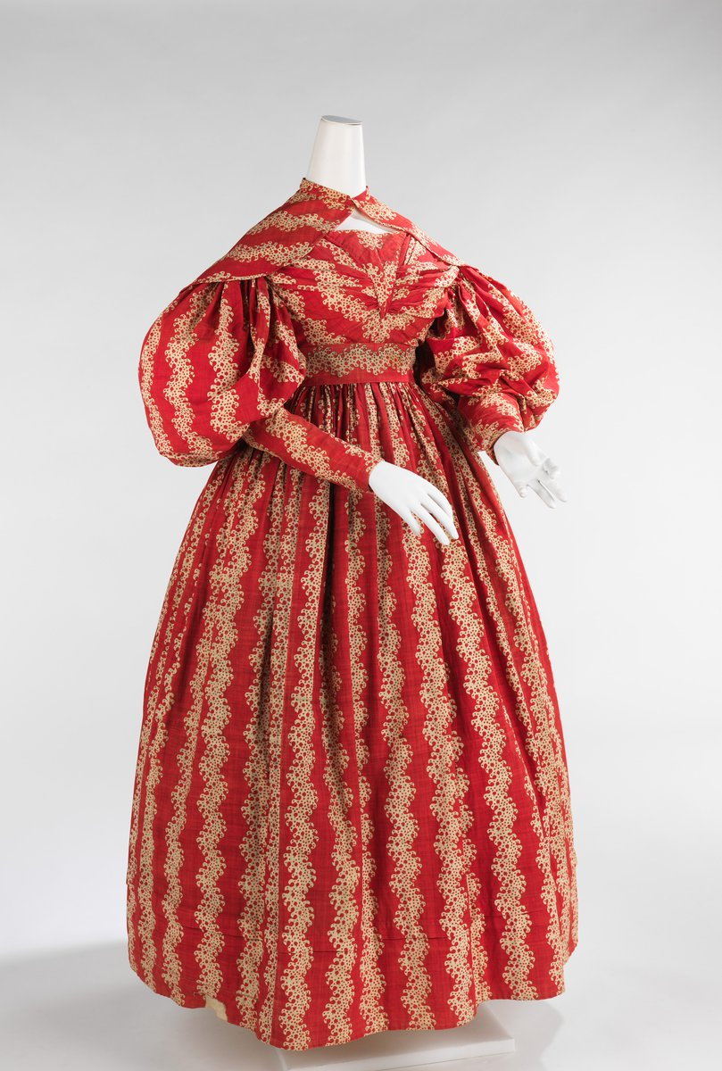 From the Met Description - This transitional style indicates the aesthetic of its period. The large gigot sleeves were popular from the early 1830s through 1836 when they began to diminish to the tightly fitted sleeves of the following period. This type of sleeve was generally supported by whalebone or down filling. Another indication of its transitional disposition is the waist height and the full bell-shaped skirts. The rich color and lively pattern is engaging and in line with the mode of the day. Dress print is bright red and gold, zigzag.