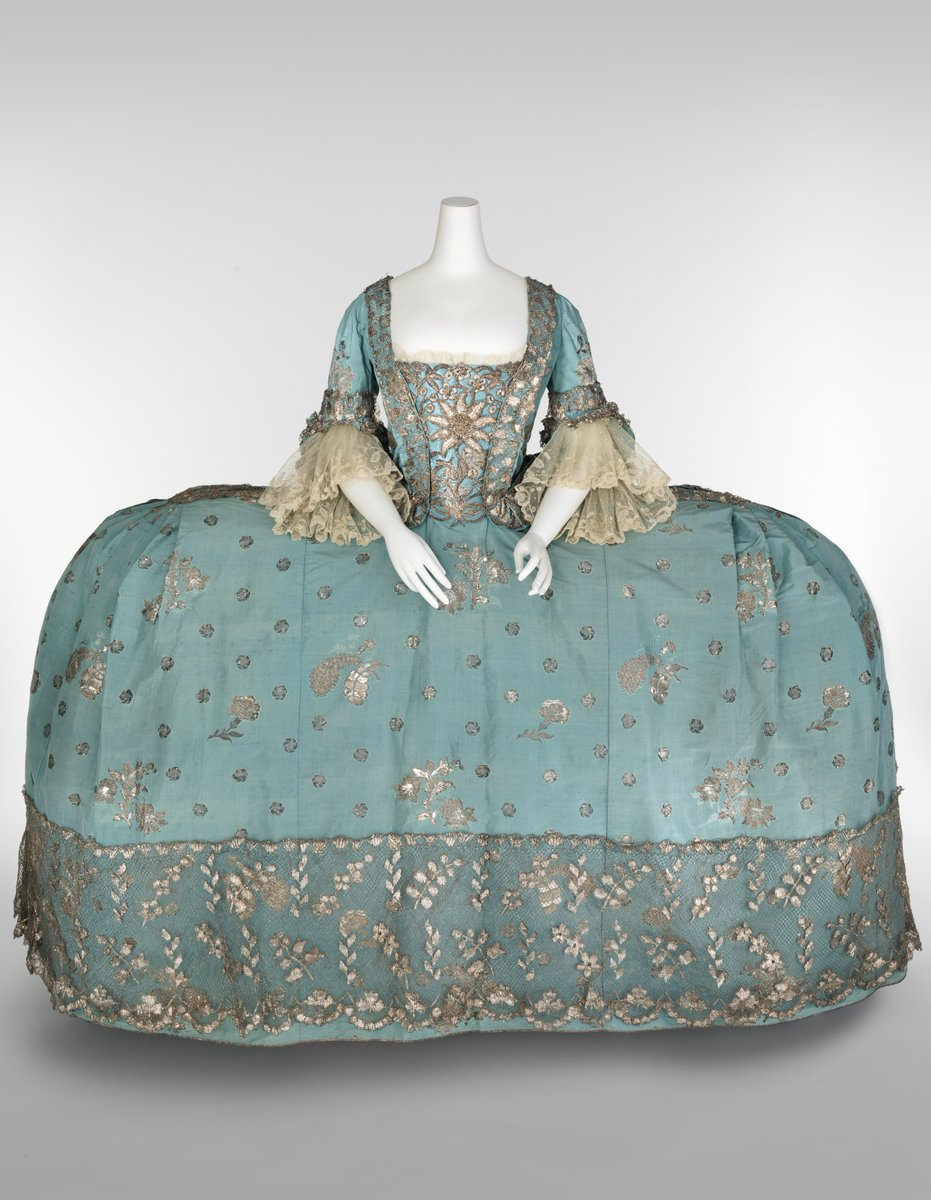 Robe a la francaise -- immense blue brocaded ballgown with exaggerated hips and metallic thread over silk. The Met Museum, public domain.