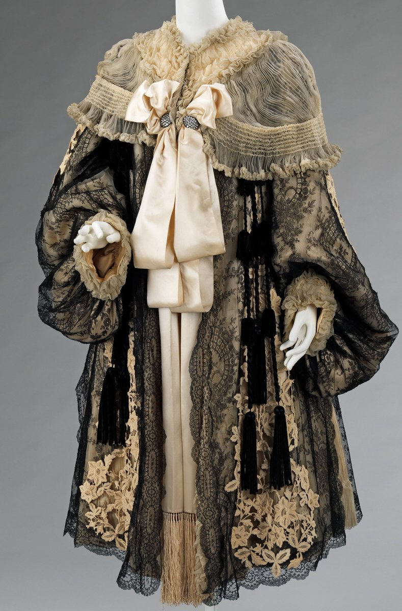 Evening coat - 1895 - 1905   An ivory and black lace evening jacket with satin bow and tassels, from the Met Museum, public domain