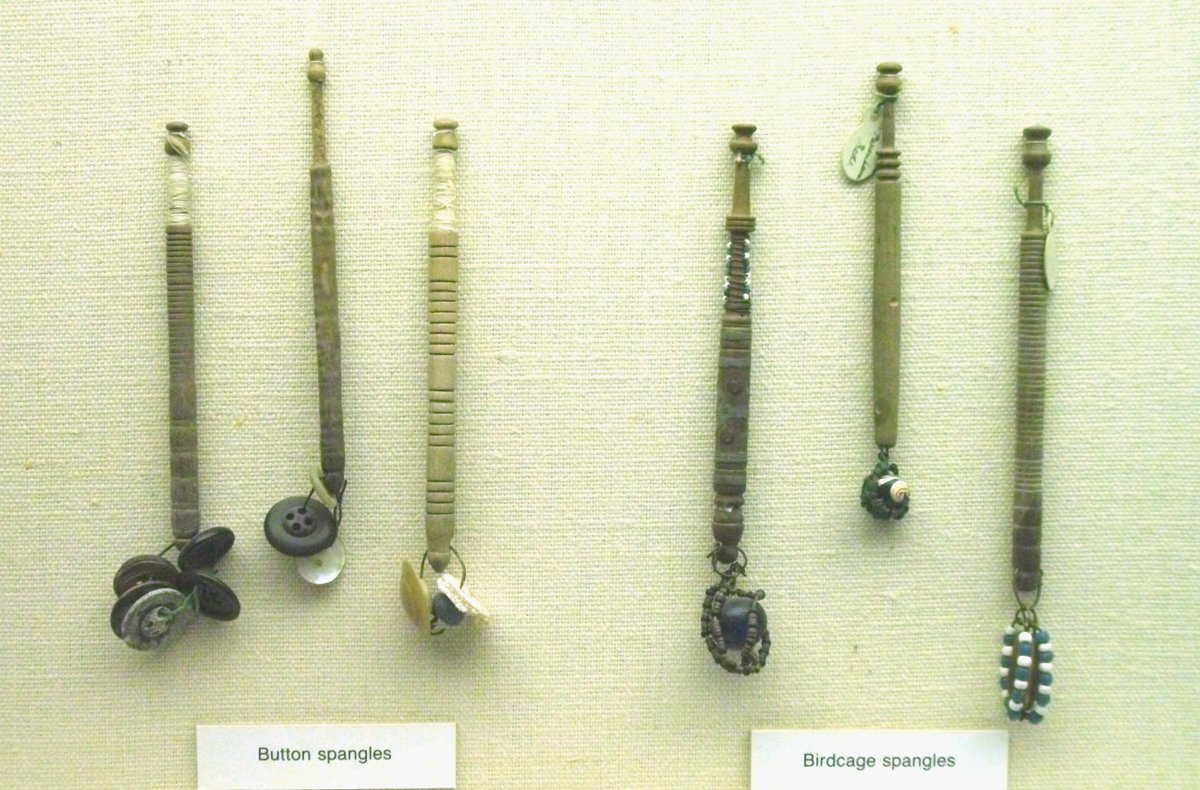 Six lace bobbins on display in Bedford Museum. The left group of three have button spangles and the right group, birdcage spangles.