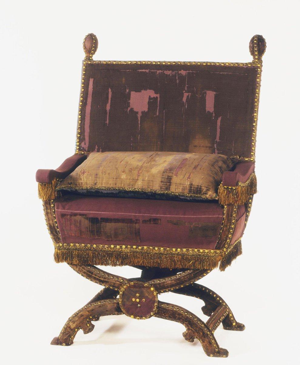 A worn velvet X-shaped chair.