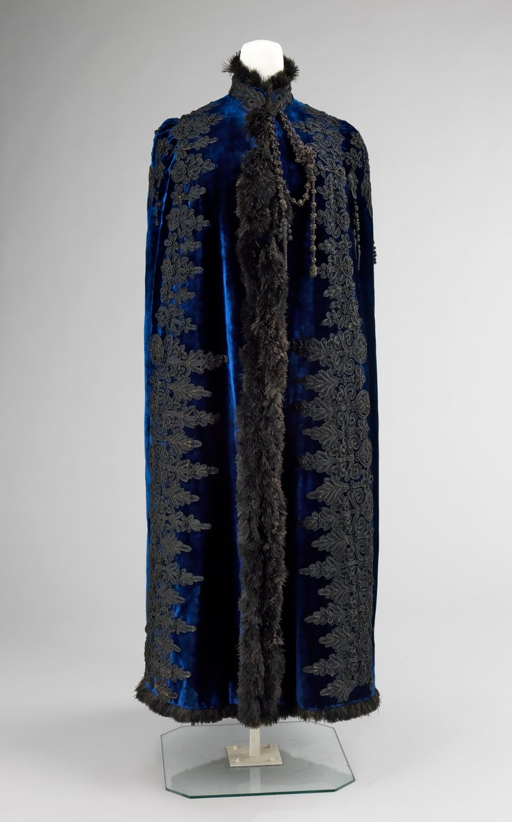 The rich color of the royal blue velvet is evocative of the original wearer who at that point in time would have been seen as a precious jewel who required continual attention and assistance. That perceived helplessness is also reflected in the cape's lack of armholes, which would limit easy mobility. Pingat's treatment of the trim completes the luxurious quality of the garment with a liberal application of guipure lace in vertical lines emphasizing the statuesque, but somewhat removed, appearance of the wearer.