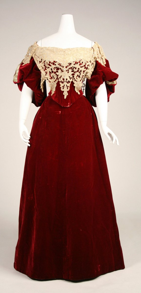 1893-95 - deep crimson velvet dress with lacework trim, narrow waist, and bulbous sleeves. From House of Worth, via Met Museum.