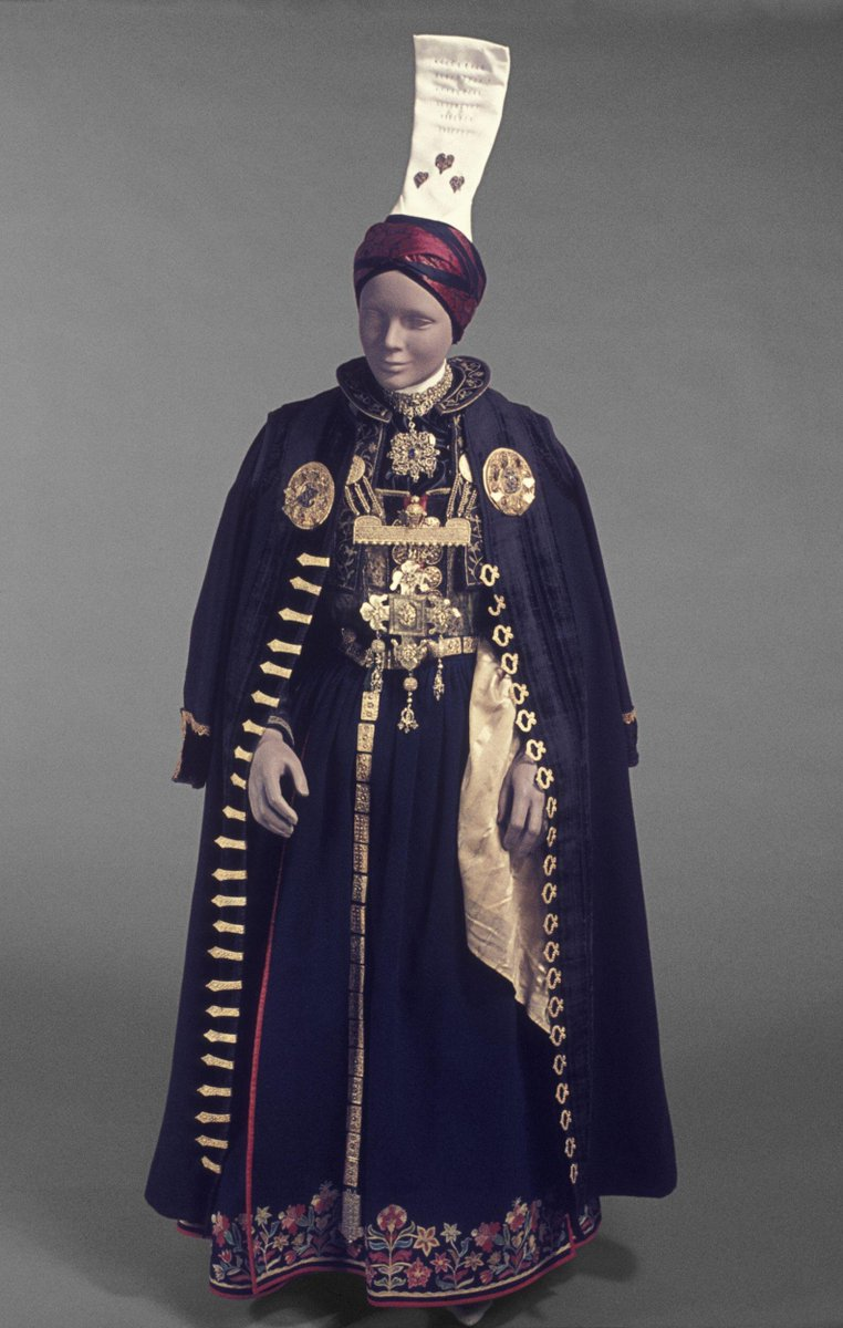 This bridal outfit is the oldest known more or less complete Icelandic woman's costume in existence. It is in the general style of Icelandic festive costumes from the late 18th century to about 1800, but is extremely rich in decoration and silver jewellery.  Pelisse (Hempa) of black cloth, bordered with velvet and fastened in front with silver gilt clasps. Two circular silver gilt disks on the breast, with cord and pendent ornaments and the monogram 'S. N. D.' in white paste.  Bodice (Upphlutur) of green velvet, with five silver gilt clasps, attached to a petticoat (Fat) of green cloth.    Petticoat (Fat) of dark blue cloth, with flowers in coloured worsted tamboured around the skirt.  Jacket (Treja) of black velvet with gold embroidery and silver-gilt buttons of globular openwork; collar (Kraga) of black velvet and gold embroidery.  Apron (Svynta) of dark blue cloth tamboured with flowers in coloured worsted, fastened with silver gilt openwork bosses. V&A Museum.