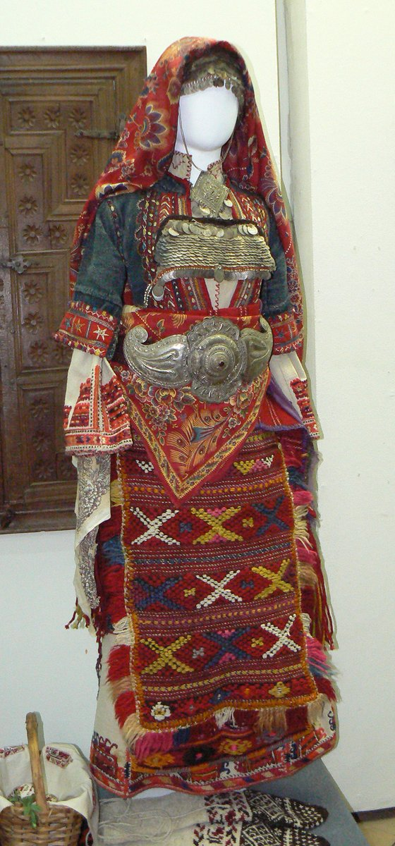 Female folk costume, Bulgaria, picture source: commons.wikimedia.org - ornate dress with metal embellishments and red embroidery.