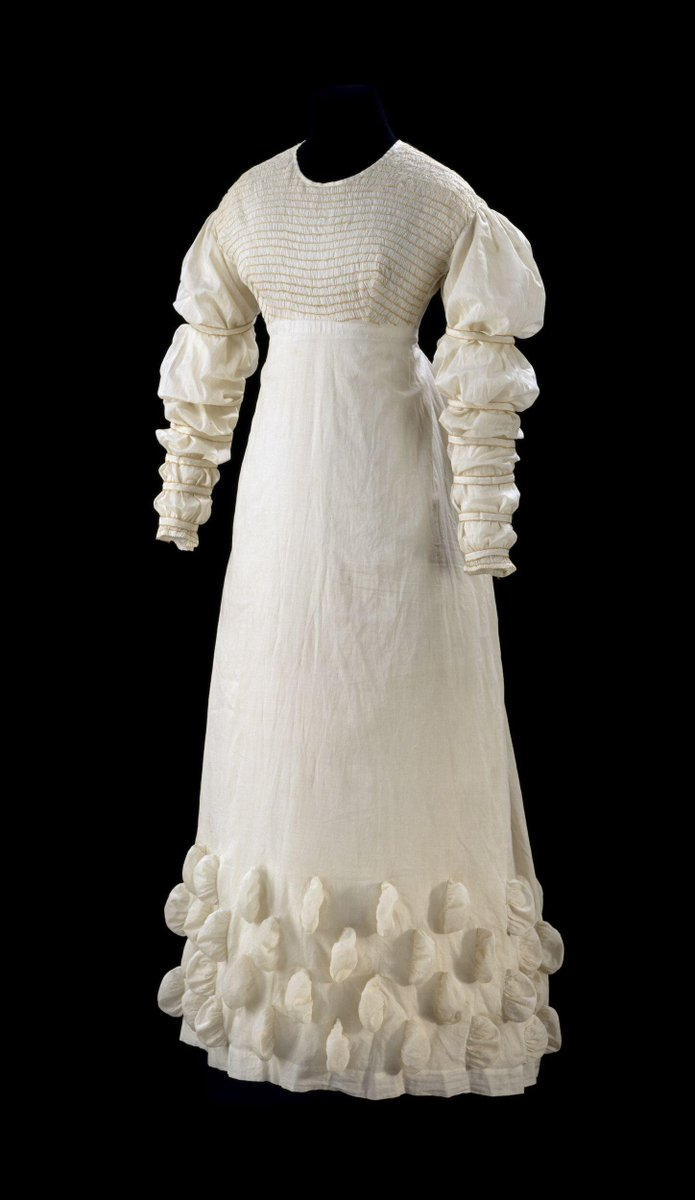 The general shape, with its raised waistline and long, white, soft clinging fabric, is loosely based on the simple tunics featured in classical art. However, this piece has a flared skirt which falls from the waist in a triangular line as opposed to the tubular silhouette of antique statues. - V & A copyright