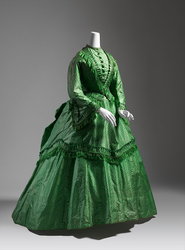 IMAGE Catharine Breyer Van Bomel Foundation Fund, 1980/ WIKIMEDIA COMMONS - A mid-19th century ballgown with bright, bright greens and fringe around the apron area, sleeves, and collar. Bustle in the back. Slightly patterned green color. Definitely poisonous.