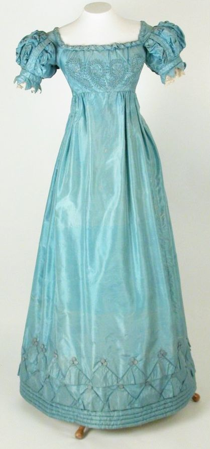 A blue regency gown (1825) in a gauzy satin. High-waisted. Embroidery in diamonds at the hem and bodice. Princess pouf sleeves. Killerton Fashion Collection © National Trust / Sophia Farley and Renée Harvey