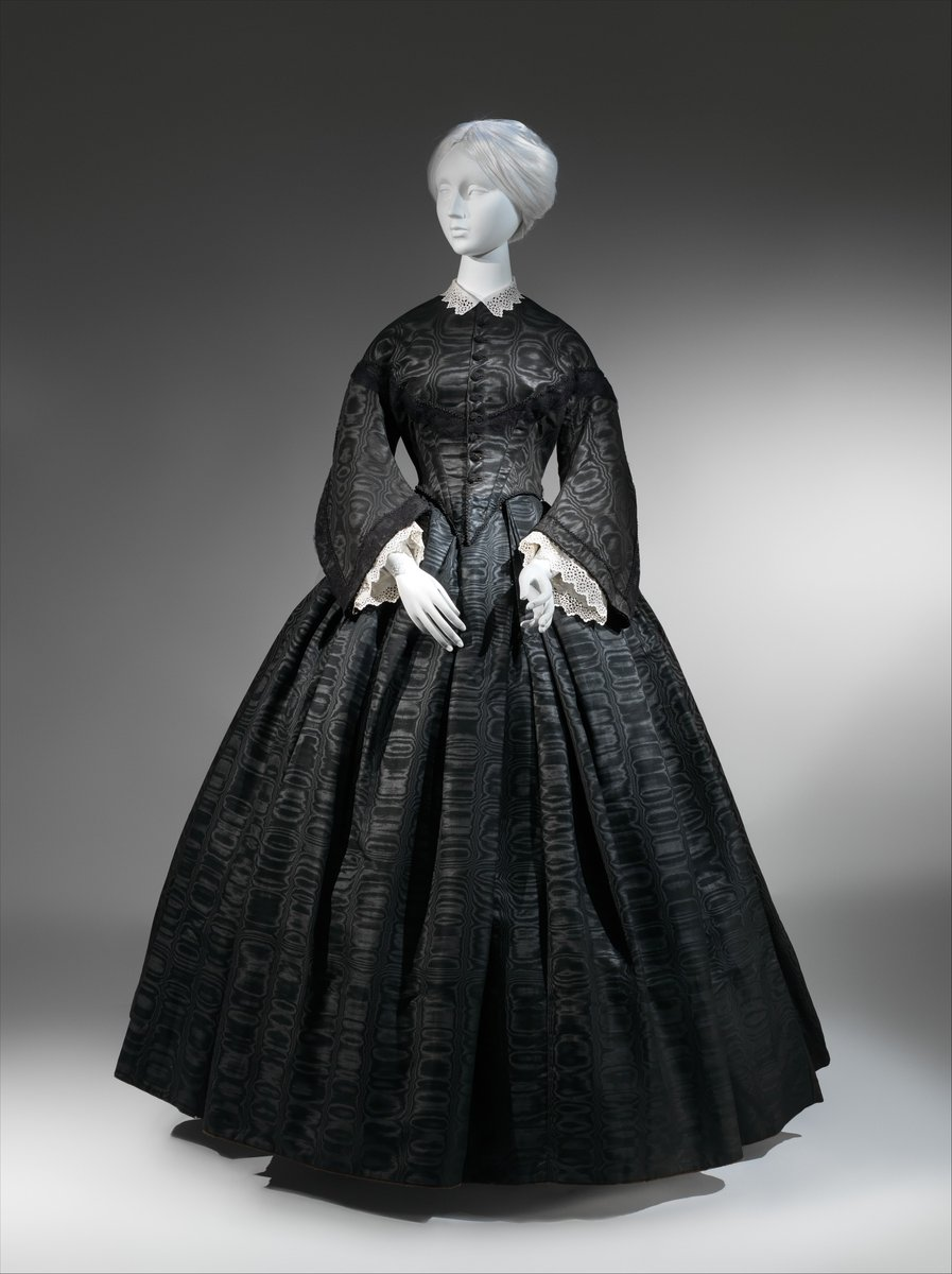 Gown, 1865 Met Museum, public domain.Fabrics, trims, and accessories distinguished mourning clothing from purely fashionable black attire. The early stages of mourning dress, typically consisting of matte blacks and mourning crape, yielded to a broader range of black fabrics, including silks of some luster such as taffeta, poult de soie, and moiré. A dulled finish suitable for the sobriety of mourning could be achieved by using wool or cotton fibers or through weave structure and finishing techniques. The striated texture of a ribbed or crimped textile was less reflective than the unbroken—and therefore glossy—face of a satin. Although the watered surface of a moiré might seem overly lustrous or luxurious for mourning, it was a fabric commonly sold by mourning retailers, and ensembles similar to this moiré dress with matching shawl were advertised for lighter mourning, especially during the 1850s and 1860s.  Black 1860s gown, marbled surface; lace on long sleeve cuffs. Narrow waist.