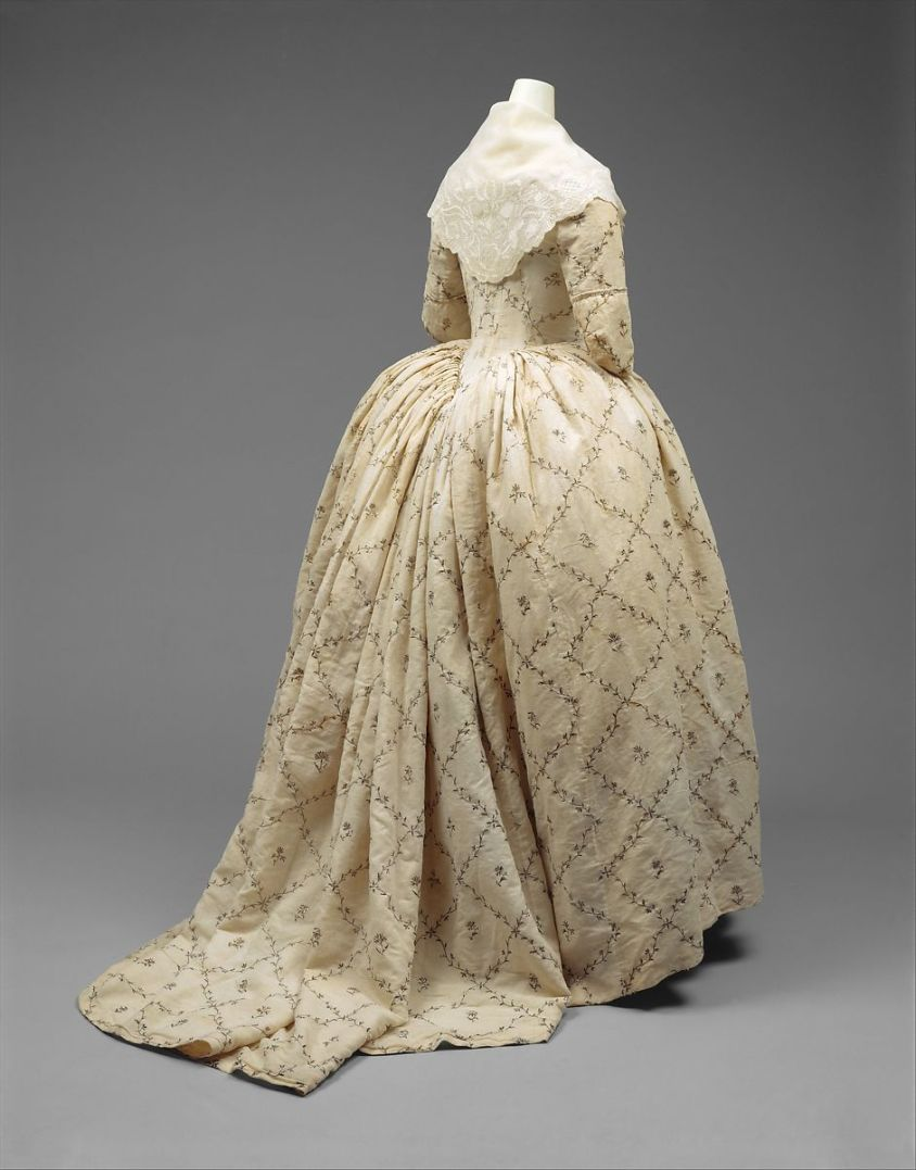 Robe à l'Anglaise 1784–87 - gown with large bustle/pannier, diamond shaped embroidery on the fabric.   Met Museum - public domain.   Cotton emerged as a fashionable fabric in the 1780s with the chemise à la reine, the cotton shift favored by Marie Antoinette beginning in this turbulent decade. As always, clothing had political and international implications. One of the chief reasons the Lyon silk manufacturers railed against the reductive modern attire is that their luxurious silks were being abandoned in favor of imported cottons from India, confirmed in the costume on the right by a weaver's mark in the selvage.