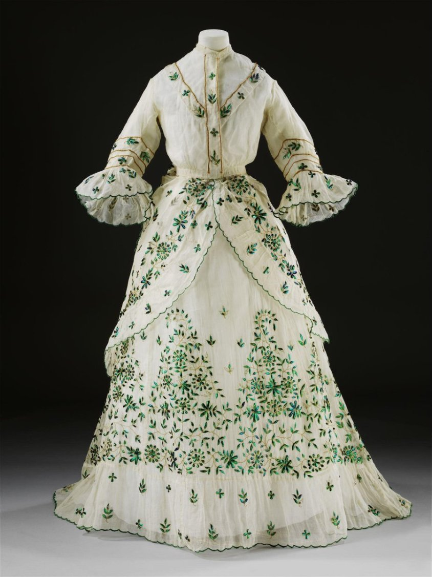 (c)Victoria and Albert Museum, London -  muslin dress with green accents. The wings of jewel beetles (buprestidae) were traditionally used to embellish textiles in South America and South and Southeast Asia. Emerald-green beetle-wing decoration became a symbol of high status in India during the Mughal period (1526-1756). Western traders in India then introduced these textiles to Europe in the late eighteenth and early nineteenth centuries. British newspapers report on several women wearing dresses decorated with beetle wings at court during the late 1820s and early 1830s. By the 1860s beetle wings were being imported to Britain in volumes of 25,000 per consignment, to be applied to textiles in imitation of the Indian technique. The wings were cut, shaped and arranged in stylised floral patterns, often accented with metal thread. The wings would have glittered in candlelight, achieving a sought-after iridescent and jewel-like effect.