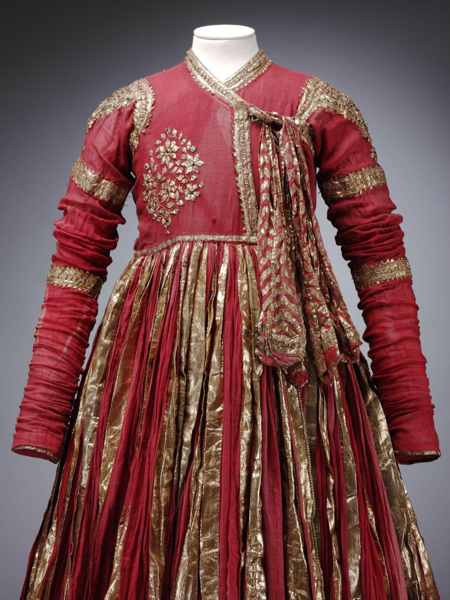 (c)Victoria and Albert Museum, London - 1855 - Rajasthan - Un-lined jama (male garment) of red muslin with trimmings in silver-gilt gota (tinsel ribbon), crimped metal strips, and sequins made of clipped jewel beetle elytron (wing cases). The full and heavy skirt is embellished with vertical strips of silver gilt gota, finished at the hem with a wide band of gota faced on the back with a sinjaf (hem facing) of green cotton and trimmed with gota-moti (beaded cord covered in gota). The torso and sleeves patterned with gota patti (cut gota-work) and beetle wing case sequins in the shape of bands on the arms, large shoulder decorations, a large flower on the right chest, a large teardrop shaped decoration at the back neck, and strips down the back and along the closure at the front. The jama fastens on the left side, tied with green cords and six large decorative ties patterned with a chevron design in silver-gilt gota.