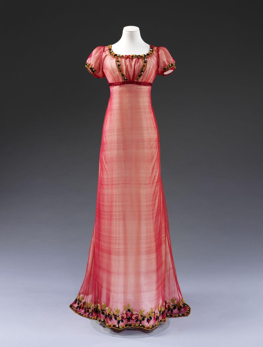 ©Victoria and Albert Museum, London - By 1810, brightly coloured and embroidered silks were as popular as white cotton and muslin for women's evening dresses. John Heathcote's bobbinet machine, patented in 1809, enabled fine net to be easily produced in wide widths for dresses, which could be hand-embroidered to achieve individual and attractive effects. Net dresses were worn with underdresses of plain silk, sometimes white, or in a matching colour.  Chenille (French for caterpillar) is a type of thick thread made by a weaving process. Cotton or silk is woven into a length of cloth which is then cut into very narrow strips, the severed weft threads creating the tufts which give the yarn its velvety texture. The dense colour of chenille thread creates a contrasting effect with the ground fabric.  Fashion leaders such as Empress Josephine, Napoleon's first wife, helped to popularise dresses of machine net, or 'tulle', which was also produced in France. She owned many machine-made net dre