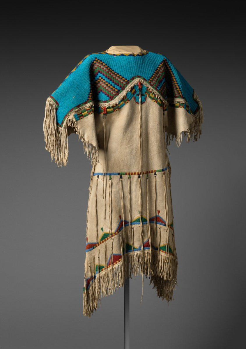 Vertical lanes of beadwork, in place of the typical horizontal configuration, give this dress its distinctive character. The U-shaped motif at the lower center represents Turtle, a symbol of power relating to women's health. Like most bead workers in the mid-nineteenth century, this maker favored tiny glass Venetian seed beads over the larger pony beads popular in earlier periods. Today, women wear elaborately beaded dresses reminiscent of this one for the Women's Traditional Dance, one of several categories in powwow competitions. - Met museum, public domain.