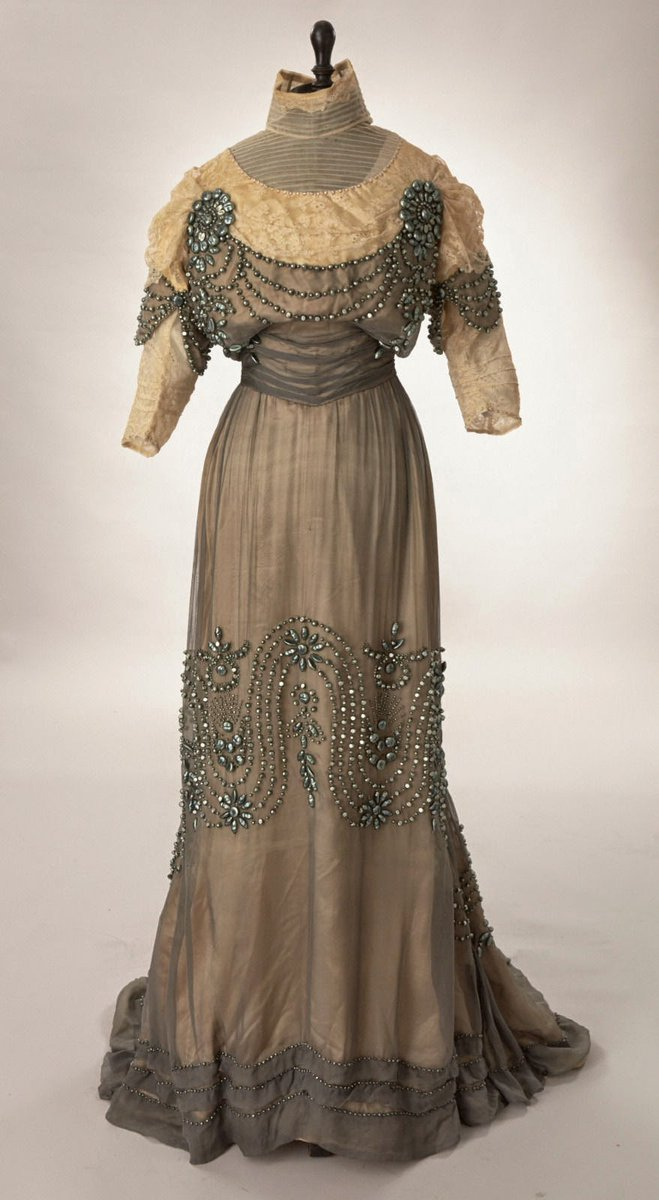 An Edwardian style dress with iridescent embroidery on the knee level and again on the chest. Lace at the top. Sheer dress draped (muslin) over a white shift. Very small waist, high neck. Via http://www.extantgowns.com