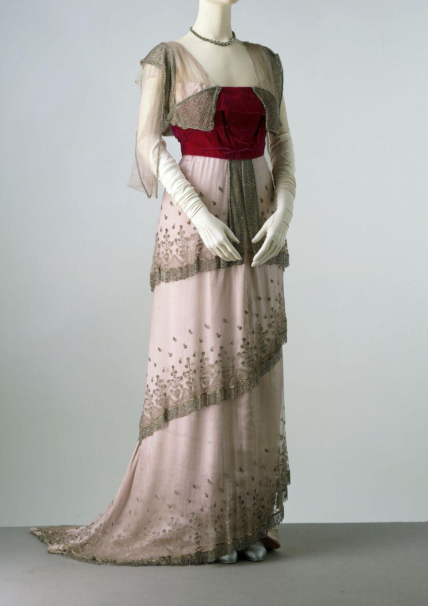 Around 1910, leading fashion houses such as Worth created evening dresses with a straight silhouette. Their impact depended on the juxtaposition of colours and a variety of luxurious and richly decorated fabrics. On this garment, vivid velvet pile is set against light-reflecting beadwork, and the triple-tiered matt net overskirt covers the sheen of the trained satin skirt. The pillar-like look exemplified by this dress replaced the exaggerated curves of the early 1900s. It also shows how designers broke the strong vertical emphasis by creating overskirts with horizontal lines. The bodice, however, is still boned (nine bones).  ©Victoria & Albert Museum, London