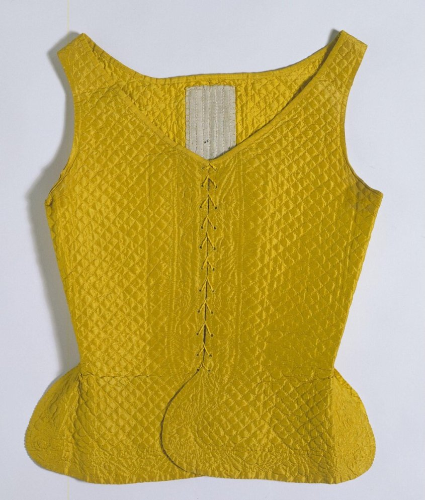 Woman's waistcoat or jumps made of yellow silk taffeta, backed with yellow silk taffeta and bound with yellow grosgrain silk ribbon. It has a shallow V neckline and rounded skirts below the waist. Inside there are 5 canvas panels, 1 at centre back reinforced with 6 strips of baleen, 2 at each side with 4 strips of baleen and 1 on each front with 5 strips. The waistcoat is quilted in a diamond pattern with yellow silk floss in running stitch. There is a quilted border of a floral design along the front edges and skirt hems. It fastens at centre front with 11 worked lacing holes on each side. - ©Victoria & Albert Museum, London