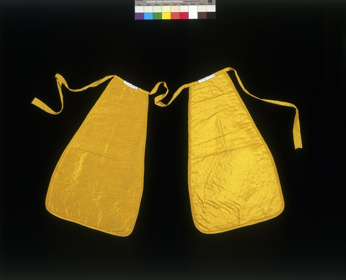 Pair of yellow silk pockets quilted with a diaper ground in the centre and scrolls around the edge, bound with yellow silk grosgrain ribbon with yellow silk taffeta ribbon. They are stitched to a linen waist tape. This pair of quilted yellow silk pockets is part of an ensemble with a matching waistcoat (T.87-1978). ©Victoria and Albert Museum, London