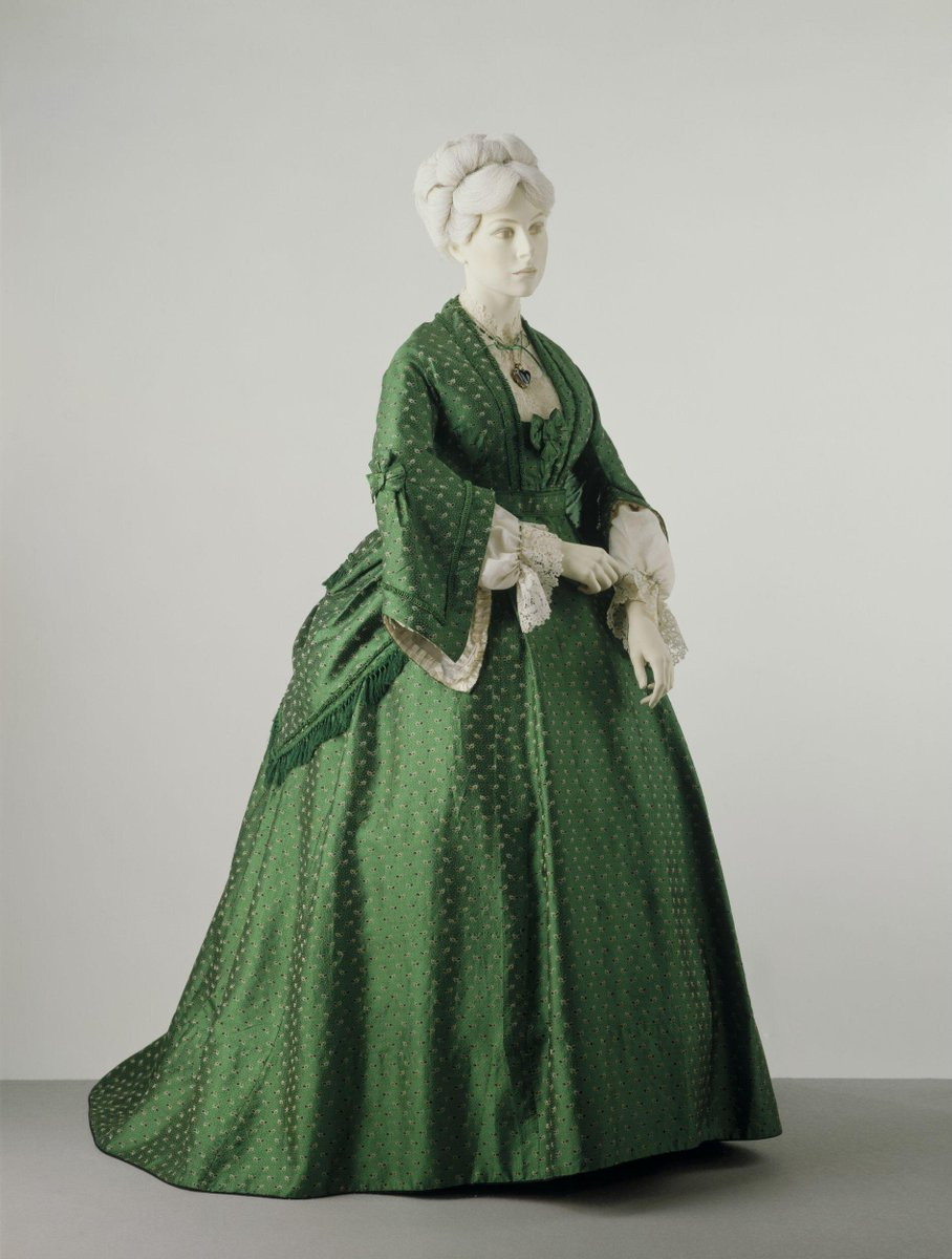 ©Victoria & Albert Museum, London Dress, peplum and belt of bright green silk. The silk has a figured pattern of black and white leaves on a speckled ground.  The dress is trimmed with looped green silk braid. With a low, square neckline with a bow at the back and long pagoda sleeves. The waist is round and the skirt is gored and pleated with a gathered panel at the centre of the back. The bodice is boned and lined with white glazed cotton, the sleeves are faced with white silk and lined with pleated white silk ribbon. The bodice fastens with hooks and has pads to enlarge the bust.  The peplum is hip-length, lined with black buckram, draped and trimmed with a silk braid and fringe.  The belt has a bow at the back and is lined with black buckram.