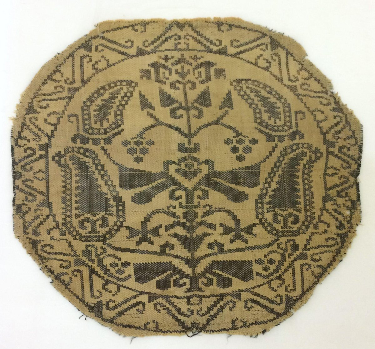 Samite (twill woven silk) was thought to originate from Persia under Sassanian rule (AD224-651). A round, gold piece of fabric woven with vines and boteh motifs. (c)Victoria and Albert Museum, London