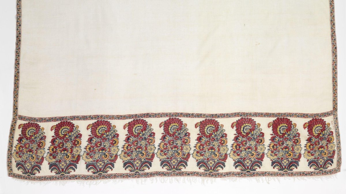 (c)Victoria and Albert Museum, London. A Kashmir pashmina dating from the mid-18th century, made in India. It is white with a border of stylized paisley/boten in red, brown, blue, and gold.