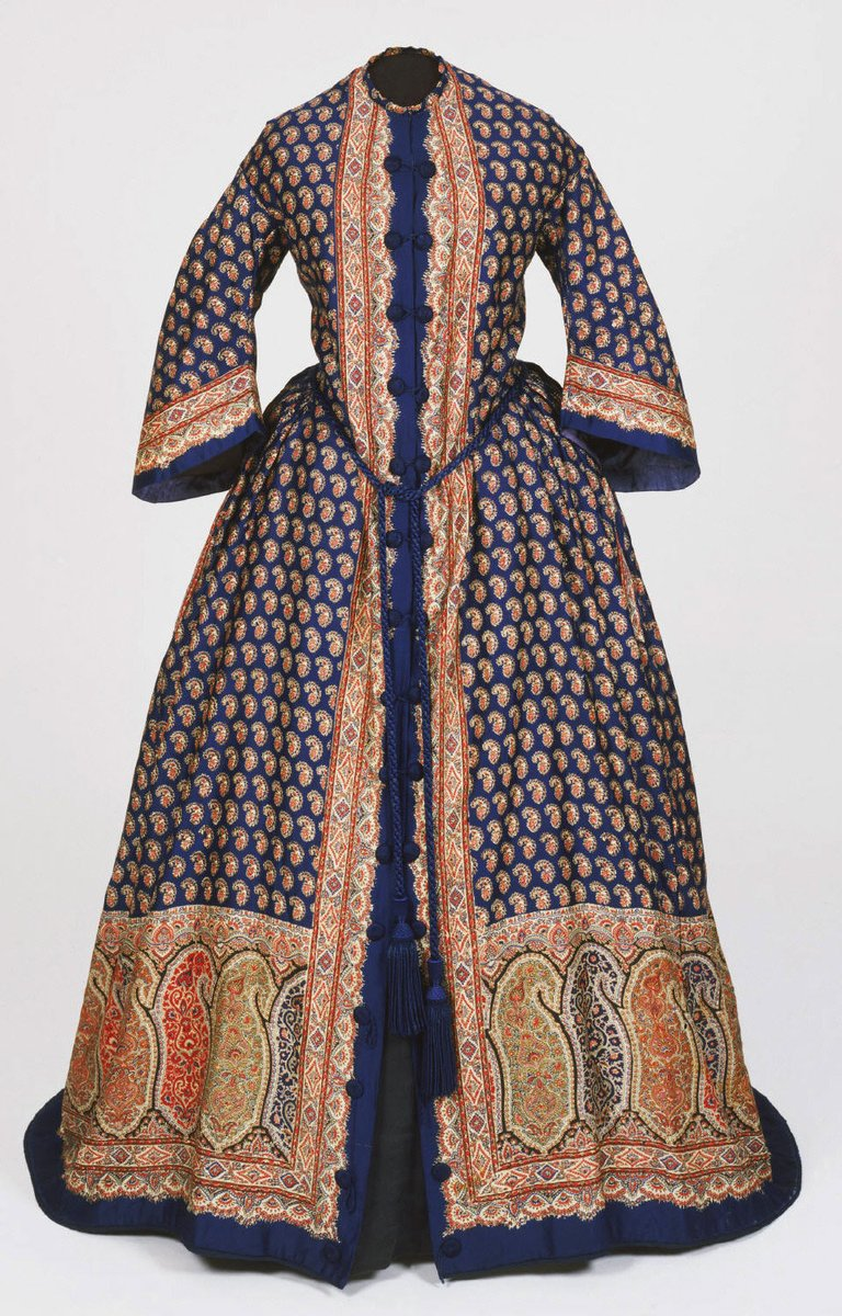 A women's paisley robe with deep blue background, bell sleeves, and both small and large paisley. The large paisley is around the bottom. From the Philadelphia museum.