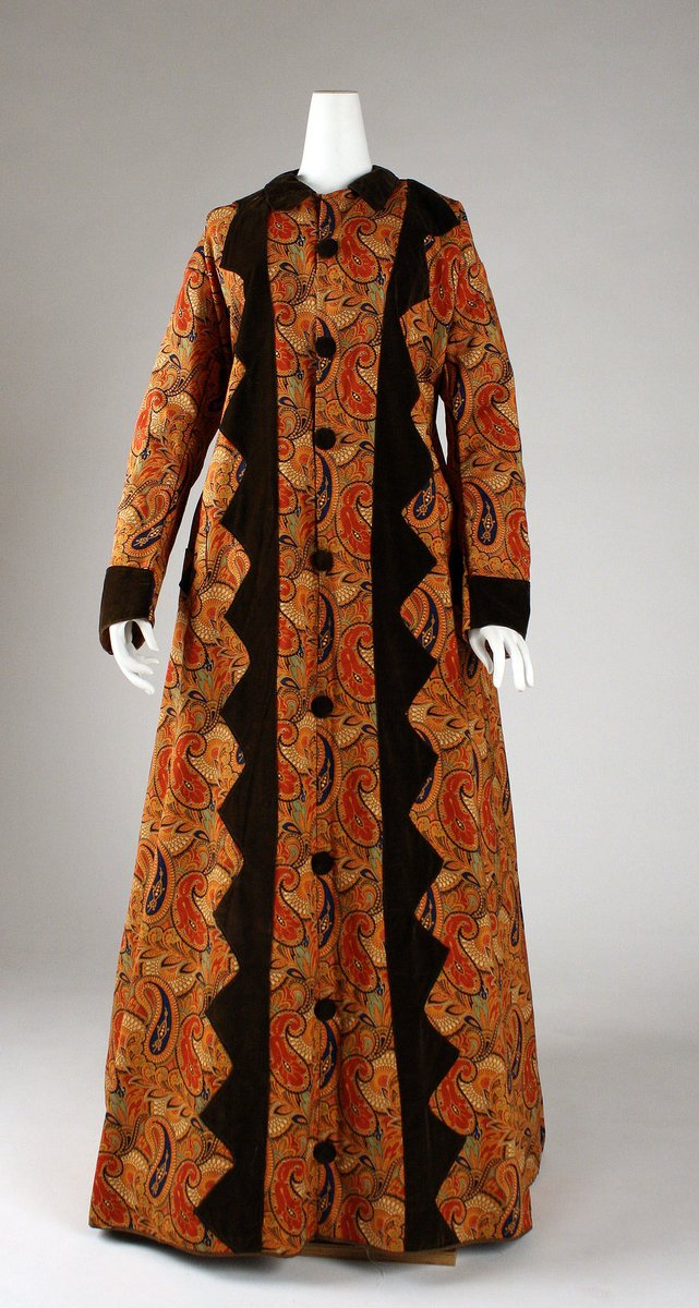 1870s dressing gown with orange paisley and brown cuffs and big brown buttons. The center is trimmed in triangles that really just make my brain hurt. Public Domain, met Museum.