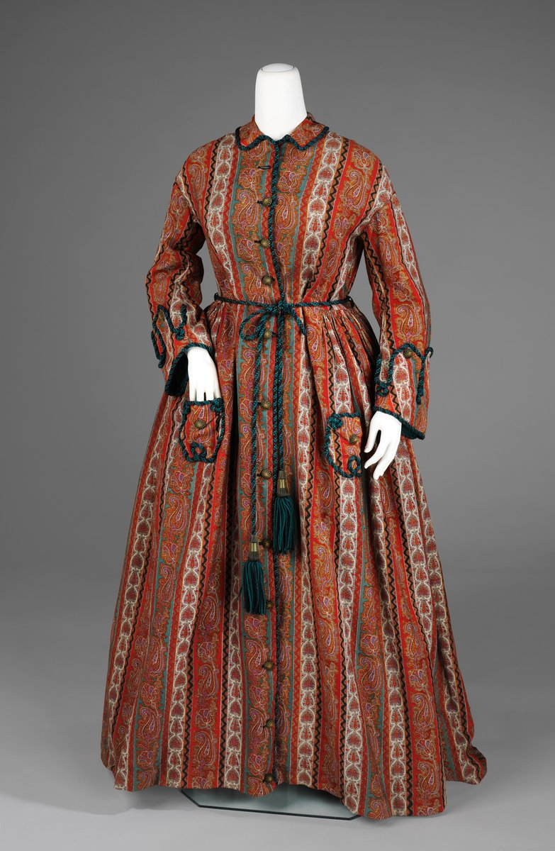 Seen here is a quintessential dressing gown of the period with military-style cuffs, cord belt and paisley pattern. This was a popular style in the mid- to late-Victorian period, for while the popularity of paisley shawls had waned, the pattern lived on in various other permutations. This dressing gown is a particularly nice example because the teal color is carried throughout in the pattern and the cord as well as the lining. Also, the warp print fabric in back adds aesthetic interest. - Met Museum, Public Domain