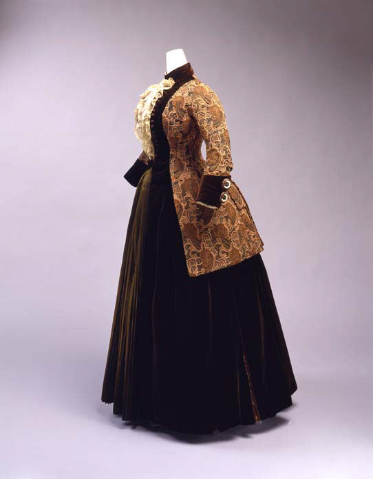 """Constructed in the manner of an eighteenth-century open robe, with the long (fifty-two-inch) embroidered jacket worn over a pleated green satin front, this American dress from """"Josephine Egan, 56 E. 10th Street"""" also refers to dix-huitième menswear, especially in its deep cuffs and jabot-like lace at center front. Its paisley embroidery likewise connects back to the first popularity of Kashmir shawls in the West in the 1780s and 1790s. By the 1880s, as indicated here, the buta, originally squat and self-contained and restricted to borders, began to mutate into attenuated, intertwining, and whiplashed forms in an escalating horror vacui that anticipates Art Nouveau. Met Museum, Public Domain."""