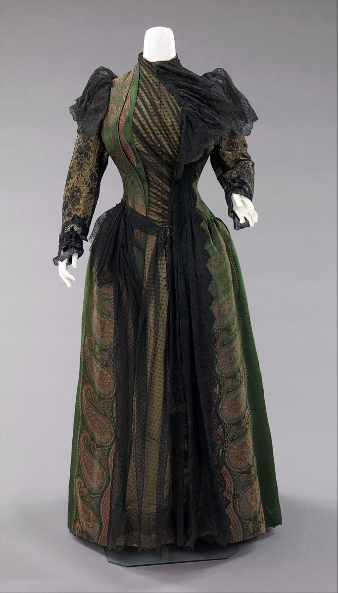 A dress of green and gold paisley with black Chantilly lace overlay. It has lace layered sleeves, and looks very modern -- super asymmetrical. Gorgeous and weird. Met museum. Public domain.