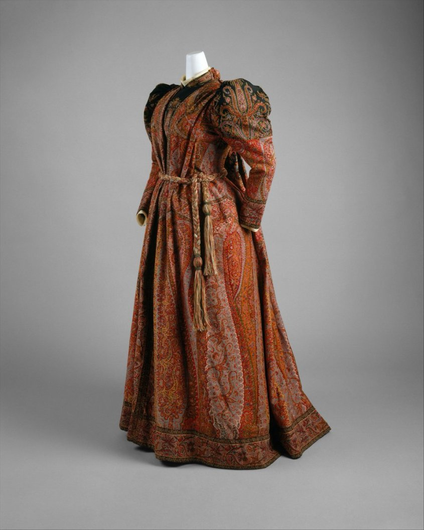 """This tea gown, composed of a cut-up wool shawl woven in a paisley pattern, imitates a black-centered Indian Kashmir shawl. In fact, the material was probably woven in France during the 1860s or 1870s. On the upper right corner of the bodice is embroidered """"Cachemire"""" in white thread. Such a tea gown, intended for gender-segregated leisure, is the feminine analogue to the man's dressing gown or smoking jacket."""