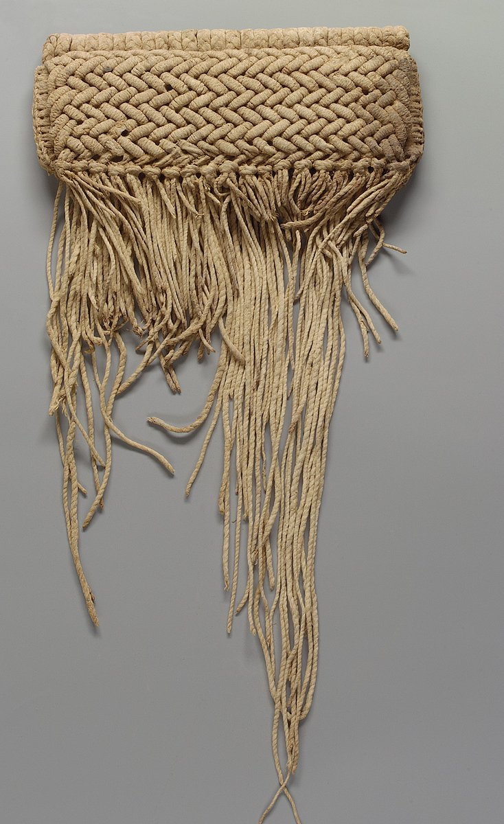 """This carefully crafted object is part of a rare group of female """"modesty skirts,"""" which are thought to have been worn low on the hips and held in place with a fiber cord. Commonly called a """"cache-sexe,"""" these fiber skirts are the oldest of their type to have survived the tropical climate of West Africa. The remarkable state of preservation of this example is due to the favorable climatic conditions of the cave in which it was found. Located within the Bandiagara Escarpment of present-day Mali, these caves are historically significant as the home of the ancient Tellem people, to whom this object is attributed, and later the Dogon.   This cache-sexe consists of three interconnected layers and is constructed from a sophisticated combination of plating and twining techniques."""