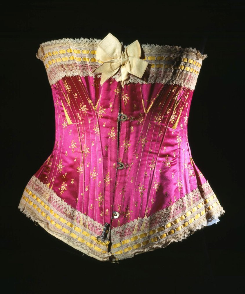 Magenta silk satin brocaded in yellow and green. Woman's corset of pink silk satin brocade, with a patten of small flowers in yellow and green, trimmed with cream lace and yellow silk satin ribbon. The centre front fastens with metal hooks and eyes and the reverse can be tightened with a length of yellow robbon, interlaced through metal eyelets. Strips of steel sewn into the body with rows of machine stitching. English, by Sykes, Josephine and Co., London, about 1890 - 1900. - National Museum of Scotland