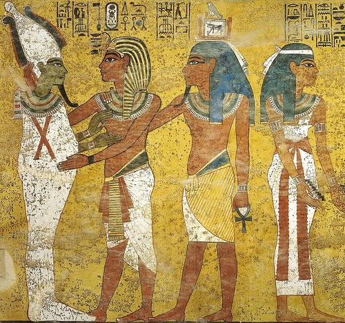 From the tomb of King Tut, four figures preparing a mummy. The two middle ones are wearing linen clothing skirts, much like fancy loin cloths.