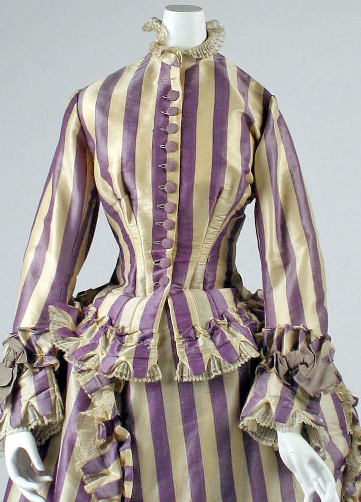 Visiting dress, 1867 - French. A silk striped dress in pale yellow and purple, with big purple buttons and pleated ruffles on the edges of the sleeves, high collar, jacket bottom, and all along the train and bustle. From the Met Museum, public domain.