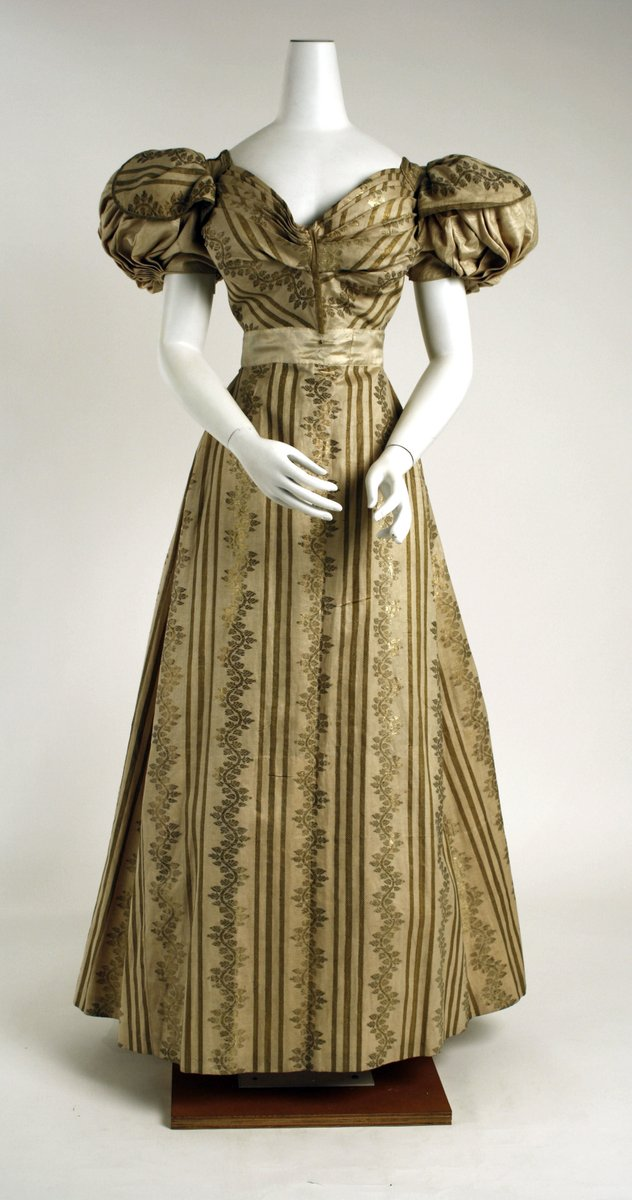 A gown with puffy sleeves in gold silk. It has a narrow waist and a subtle flair. The pattern looks like vines and stripes, with a paler silk belt around the middle. From the Met Museum, public domain.