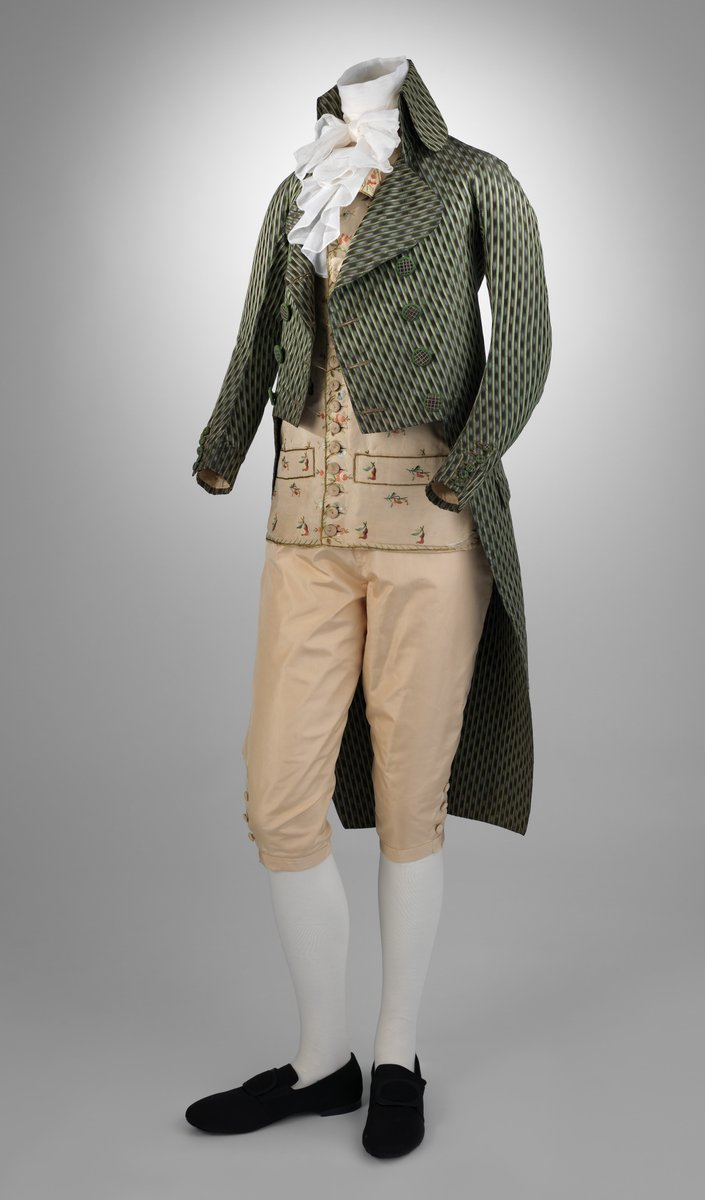 This young man's tailcoat, with its high turned-down collar, narrow back, and wide lapels, exemplifies the exaggerated silhouette fashionable in post-revolutionary France. Striped textiles, modish from the 1760s, were ubiquitous in the dress of both sexes by the end of the century. In menswear, stripes served as a decorative substitute for the ornate, polychrome embroidery of earlier suits. The trend reflects the influence of Orientalism and neoclassical taste; in earlier centuries, stripes had pejorative connotations in the West and were associated with the clothing of socially marginalized groups. Met Museum, public domain.