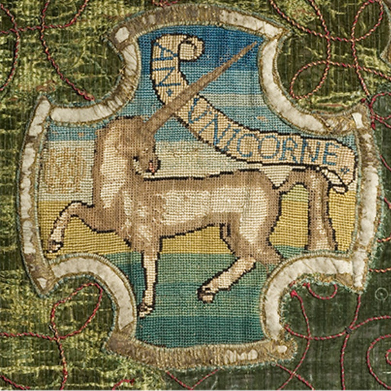 """An embroidered unicorn that says """"AN UNICORNE"""" in a little scroll. On green velvet."""