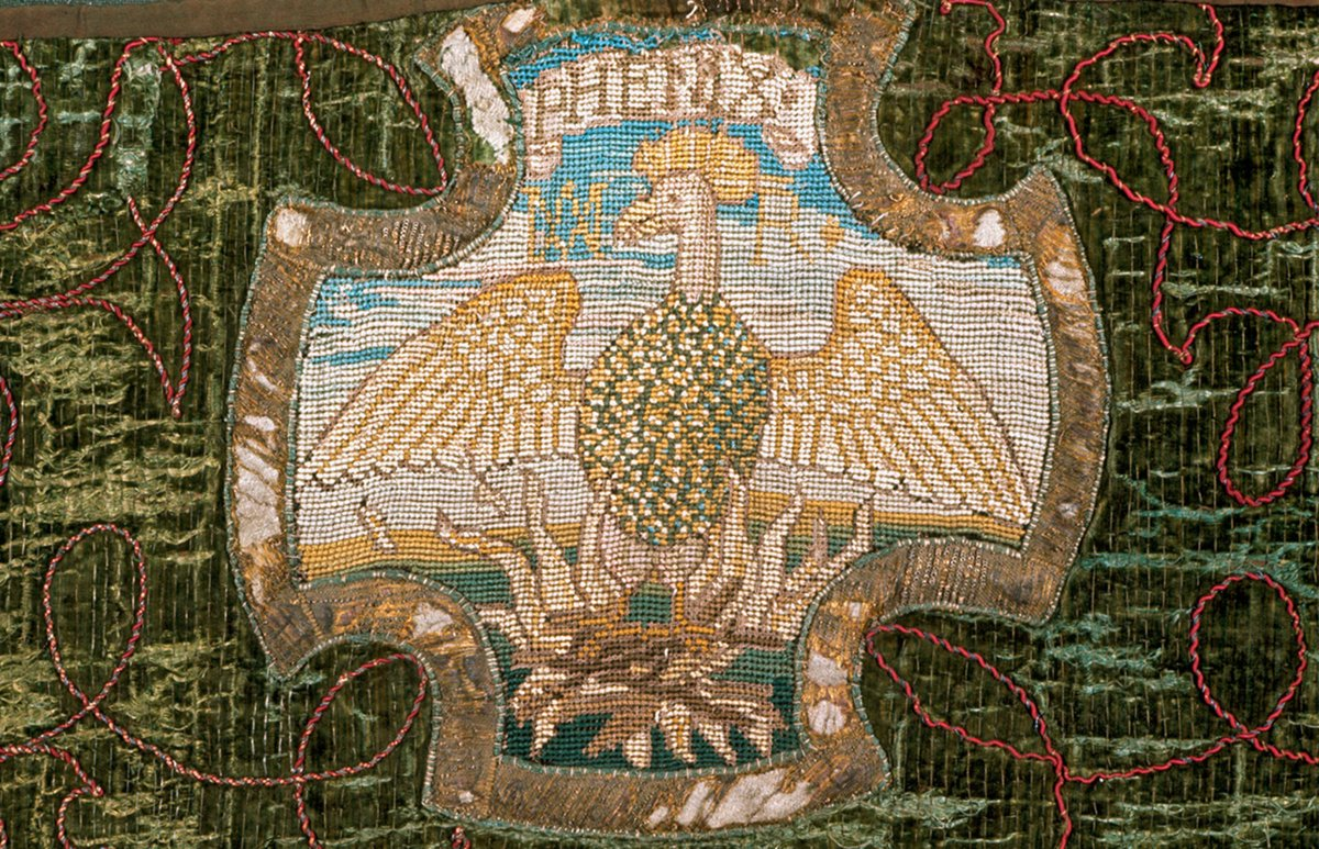 """A phoenix portrayed above burning flames with the word """"PHENIX"""" above it on a cross-like shape."""