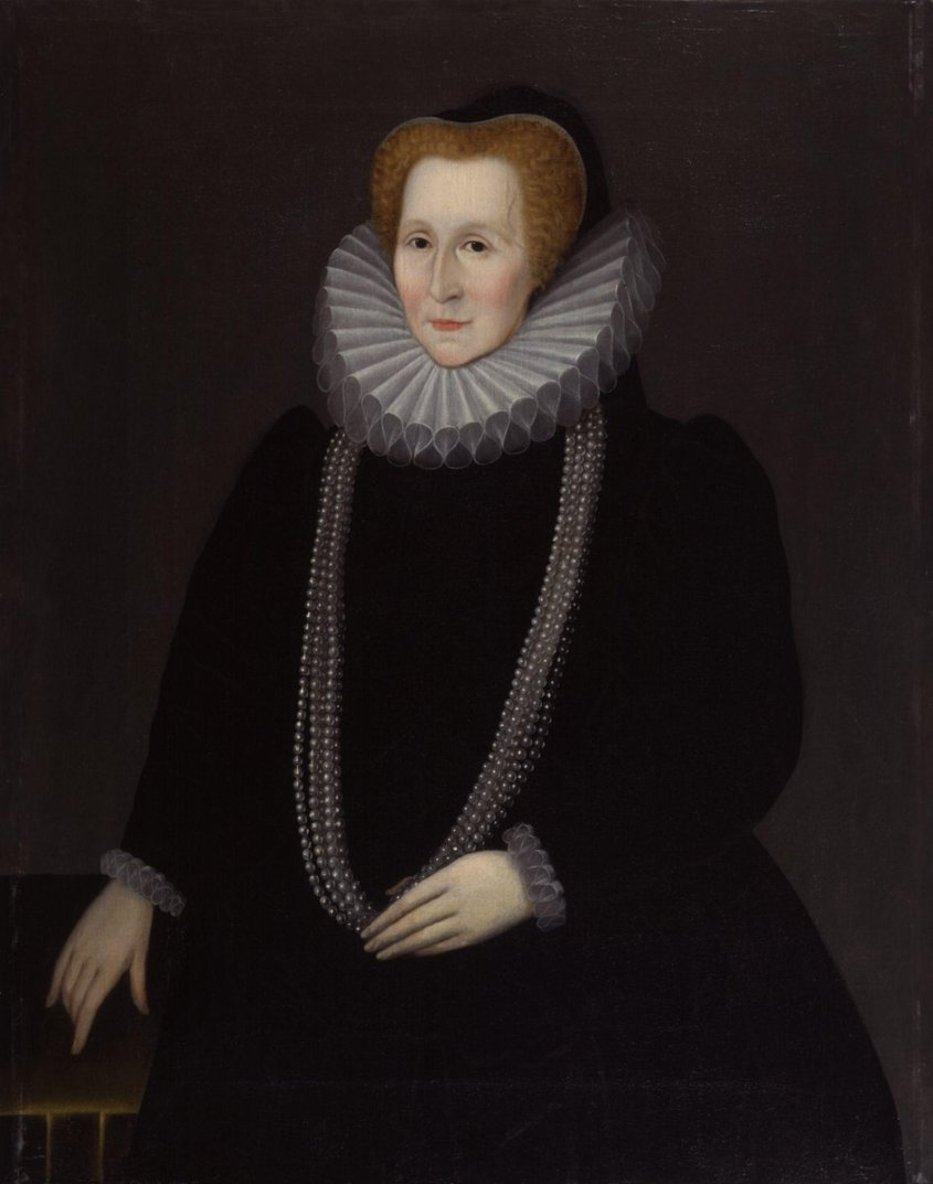 Bess of Hardwick in a large ruff, sober velvet gown, and a long string of pearls.