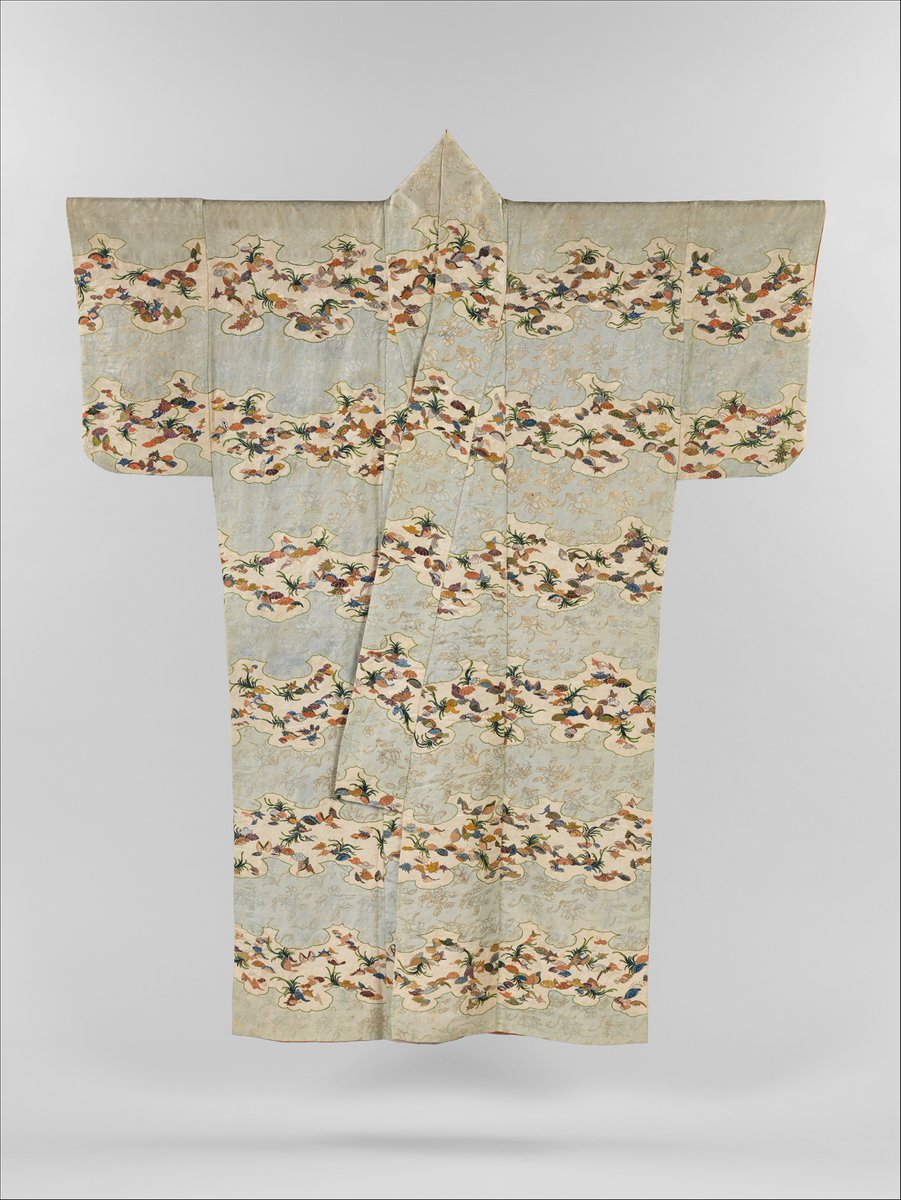 This sumptuous robe is among the earliest extant kosode (garment with small sleeve openings). The natural scenery of Japan's coast, with its beaches strewn with shells and sea grass, inspired the delicate embroidered design. The foundation fabric, woven in an intricate key-fret pattern with floral motifs, was likely imported from China in its white, undecorated state. It was then resist dyed to achieve the effect of irregular sandbanks, and the marine motifs were embroidered on top. The alternating bands of light blue were further embellished with gold-leaf accents. From the Met.