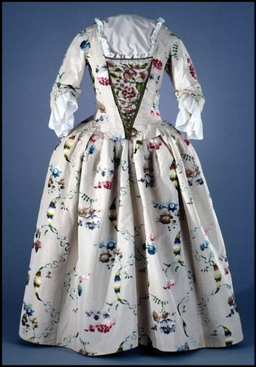 """Ivory silk brocaded with silk; cream linen sleeve and bodice lining; cream silk lining; ivory silk facings at front bodice opening. Woman's closed-front gown of ivory silk brocaded in pink, purple, and blue flowers and green vines and leaves. Gown has elbow-length sleeves, an open v-shaped front for wear with a stomacher, and a pleated skirt with drop-front panel. The bodice has 2"""" robings at the front, which would fasten to a stomacher to close the front bodice. These robings run over the shoulders into the back, which has a square-shaped neck edge. The sleeves are slightly pleated at the armseye, and end at the elbow with a 5"""" cuff that is pleated and narrowed into 1 1/2"""" on the inside elbows. Via Colonial Williamsburg Collection."""